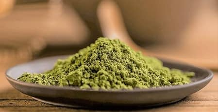 Kratom powder in a bowl with a blurred background