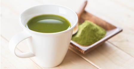 Kratom Tea in white glass next to a bowl of green powder