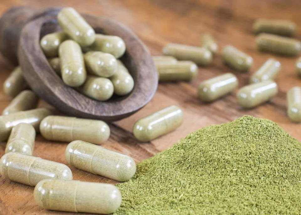 Kratom capsules and powder on a table from Golden Road Botanicals